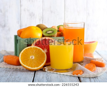 Fruit and vegetable juice in glasses and fresh fruits in box on wooden table on wooden wall background #226555243