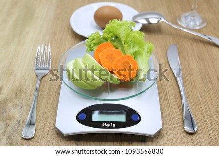 fruit and vegetable on weighing machine for calories count with knife, fork and spoon on wooden background.