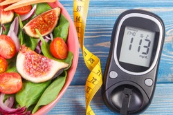 Fruit and vegetable salad, glucometer with result of measurement sugar level and tape measure, concept of diabetes, diet, slimming, healthy lifestyles and nutrition