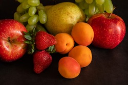 Fruit assortment of fresh fruits - grapes, strawberries, apricots, pear, apple - on black background