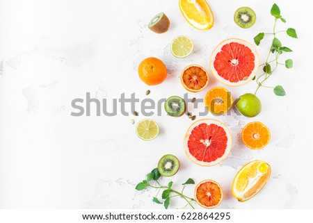 Fruit background. Colorful fresh fruit on white table. Orange, tangerine, lime, kiwi, grapefruit. Flat lay, top view, copy space.