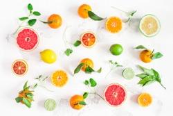 Fruit background. Colorful fresh fruits on white table. Orange, tangerine, lime, lemon, grapefruit. Flat lay, top view.