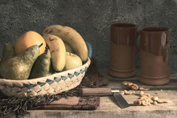 fruit basket with apples, bananas, pears and orange on on an old wooden table where there are also some roasted nuts