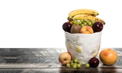 Fruit Basket with Orange, Apple, Plumb, Kiwi, Grapes, and Peaches. Fun vegan and vegetarian healthy food concept with blank space for text,.
