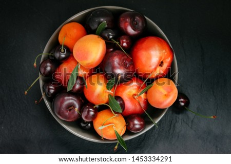 Fruit bowl. Seasonal fruits with green leaves in a bowl n rustic dark background, top view. Organic fresh fruit, peach, plum, aprocot, cherry. Foto stock ©