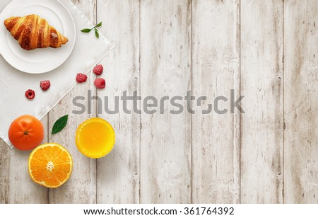 Photo of Fruit breakfast with free space on wooden table. Croissant, orange, raspberries, juice, with top view.