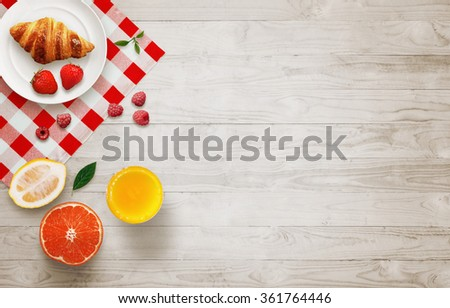 Photo of Fruit breakfast with free space on wooden table. Croissant, orange, strawberries, raspberries, lemon, juice, with top view.