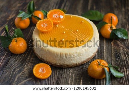 Fruit cheesecake decorated with fresh tangerines on wooden background