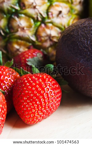 Fruit composition on light wood with group of ripe, red strawberries and avocado to the fore, and a pineapple in soft focus background.