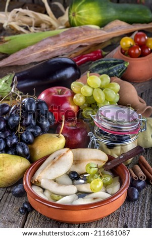 Fruit compote of pears with grapes surrounded by fresh fruit and vegetables