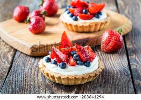 Fruit dessert tarts with cream, strawberry and blueberry on wooden table