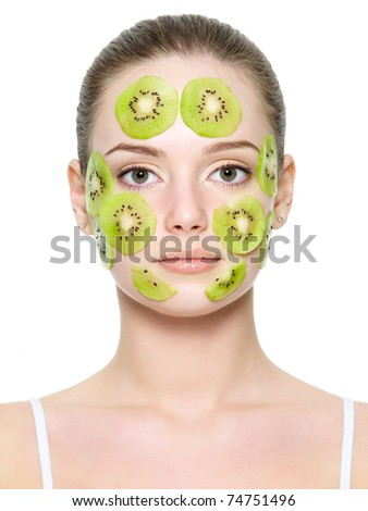 Fruit facial mask of kiwi on a face of beautiful young woman - white background