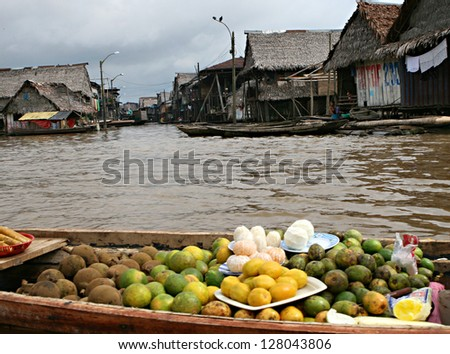 Fruit for sale on a boat. Houses on stilts rise above the polluted water in Belen, Iquitos, Peru. Thousands of people live here in extreme poverty without clean water or sanitation.