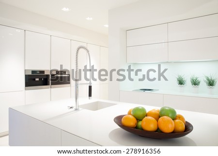 Fruit in a bowl on the marble island in white kitchen