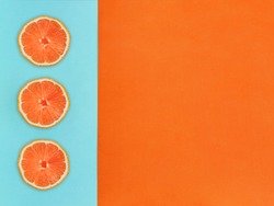 Fruit in flat lay Three slices of grapefruit are lying vertically in a row on two-tone background Top view Trendy colorful flat lay photo of grapefruit with space for text.