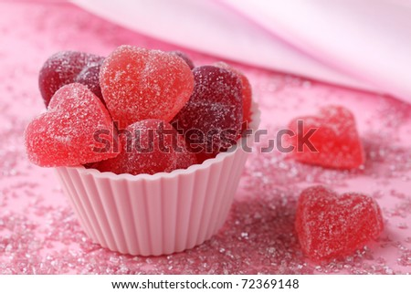 Fruit jellies candy hearts on pink background