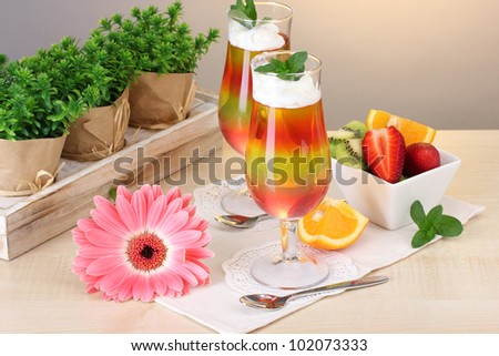 fruit jelly in glasses and fruits on table in cafe - stock photo