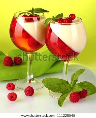 fruit jelly with berries in glasses on green background
