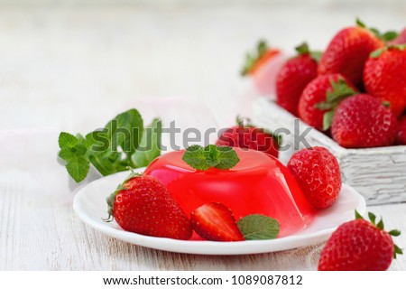 Fruit jelly with fresh strawberry. Healthy food. Strawberry jelly on white plate. Summer dessert with fruit jelly and fresh strawberry.
