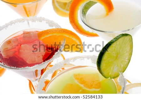 Fruit juice in cocktail glasses over white background