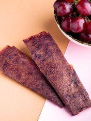 Fruit pastille of red grape and fresh grape. Russian pastila. Healthy raw vegan snack. Organic super food sweets. Vegetarian dietary food. Fruit leather. Sweets candy roll. Space for text. Copy space.