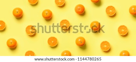 Fruit pattern of fresh orange slices on yellow background. Top view. Copy Space. Pop art design, creative summer concept. Half of citrus in minimal flat lay style. Banner