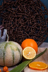 Fruit photography of some edible fruits: orange, honeydew melon, Chinese lantern fruits and a green leaf of aloe Vera, in front of a woven flat basket.