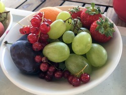 Fruit plate of fresh grapes, plumbs and strawberries