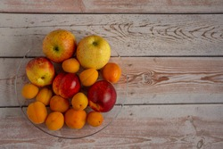 Fruit plate on the table. The fruit as a whole. Assorted apricots, apples, nectarines. Imported fruit. Vegetarian menu. raw food. healthy food. Food for dental health.