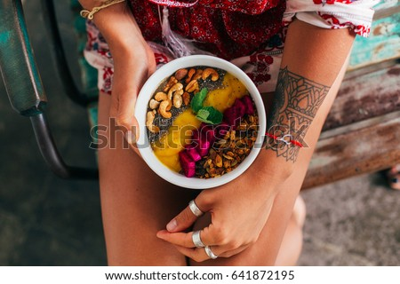 Fruit plate with granola. Exotic fruits. Girl's healthy breakfast