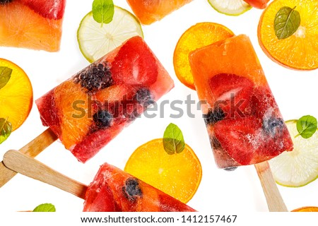 Fruit popsicles, homemade fruit ice lolly of various fruits; mandarins, limes, blackberries, blueberries, raspberries and strawberries with the addition of lemonade on white background, top view.