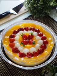 fruit pudding. caramel -combination pudding with variant fruits as topping. Fruits consist of slice of peach, kiwi, strawbery, longan and grape. shiny, gritty and grainy textured.