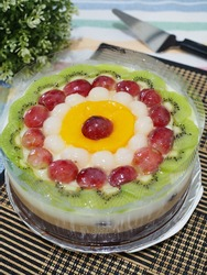 fruit pudding. caramel combination puding with variant fruit as topping. fruit consist of kiwi, grape, longan, strawberry and peach. gritty and grainy textured.