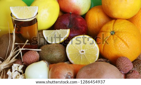 Fruit red tea with orange, lemon, kiwi, apple, mango, carrot and litchi in glass cup, on wooden table, on fruit background #1286454937
