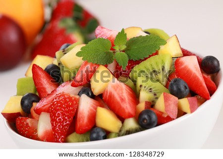 Fruit salad in a bowl with strawberries, kiwi, blueberries and peaches