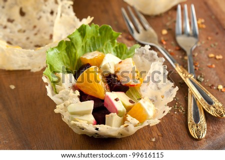 Fruit salad in cheese tartlet served on wooden cutting board