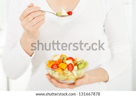 Fruit salad in the hands of women.