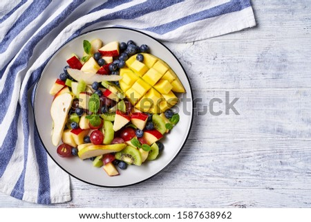 Fruit salad on a plate of mango, blueberries, red grape, pears, apple, with fresh mint, on a white wooden table, horizontal view, copy space, copy space