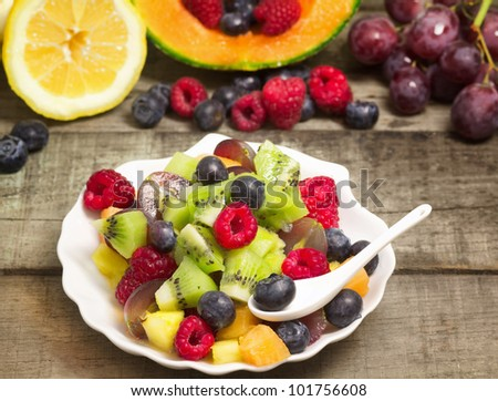 fruit salad with fruits background on wood