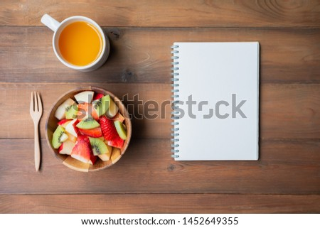 Fruit salad with orange juice and notebook on brown wood background with copy space,Flat lay. #1452649355