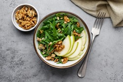 Fruit salad with pears, arugula, walnuts and Roquefort cheese. Delicacy appetizer in bowl on gray background