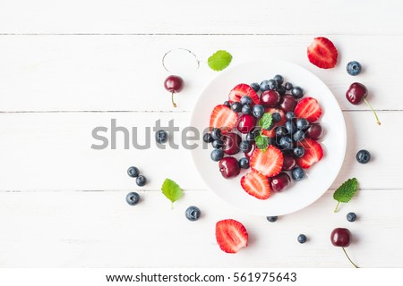 Fruit salad with strawberry, blueberry, sweet cherry on wooden white background. Flat lay, top view.