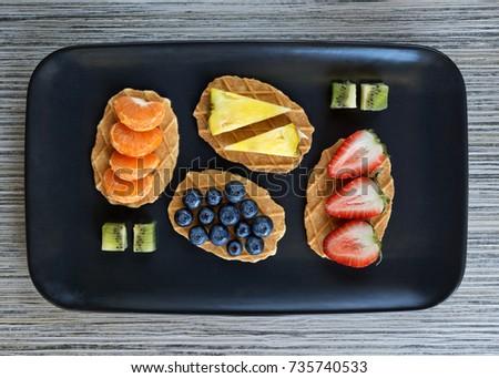 Fruit served on waffles on a black serving dish #735740533