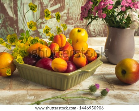 Fruit set of ripe fruits. Apricots and nectarines in a green plate. A small bouquet of carnations in a gray vase. #1446950906