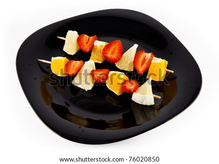 Fruit skewers of strawberries, grapefruit and oranges on the black plate and white background.