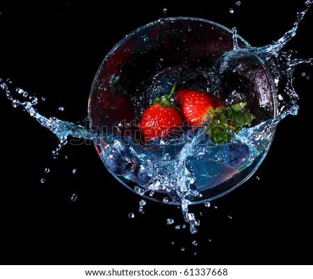 Fruit splashing into a glass of blue liquid. Concept - make a splash