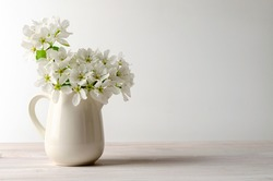 fruit tree pear flowers in a white jar on white table