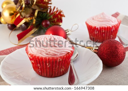 fruitcakes in paper baskets on a New Year\'s table with Christmas tree decorations