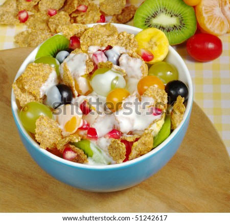 Fruits and Cereals with Joghurt in blue bowl on wooden board