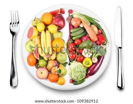 Fruits and vegetables are on opposite sides of the plate. Image on white background.
